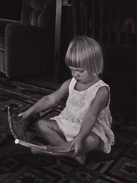 A little girl from Indianapolis reads on the floor of a living room