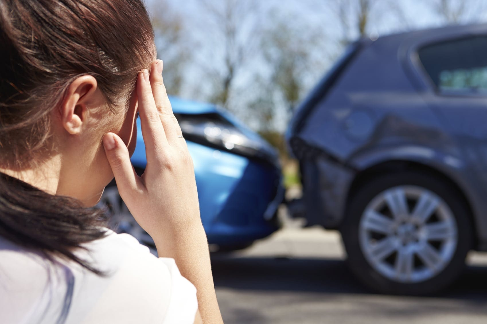 Woman Examining Rear End Car Accident Stock Photo