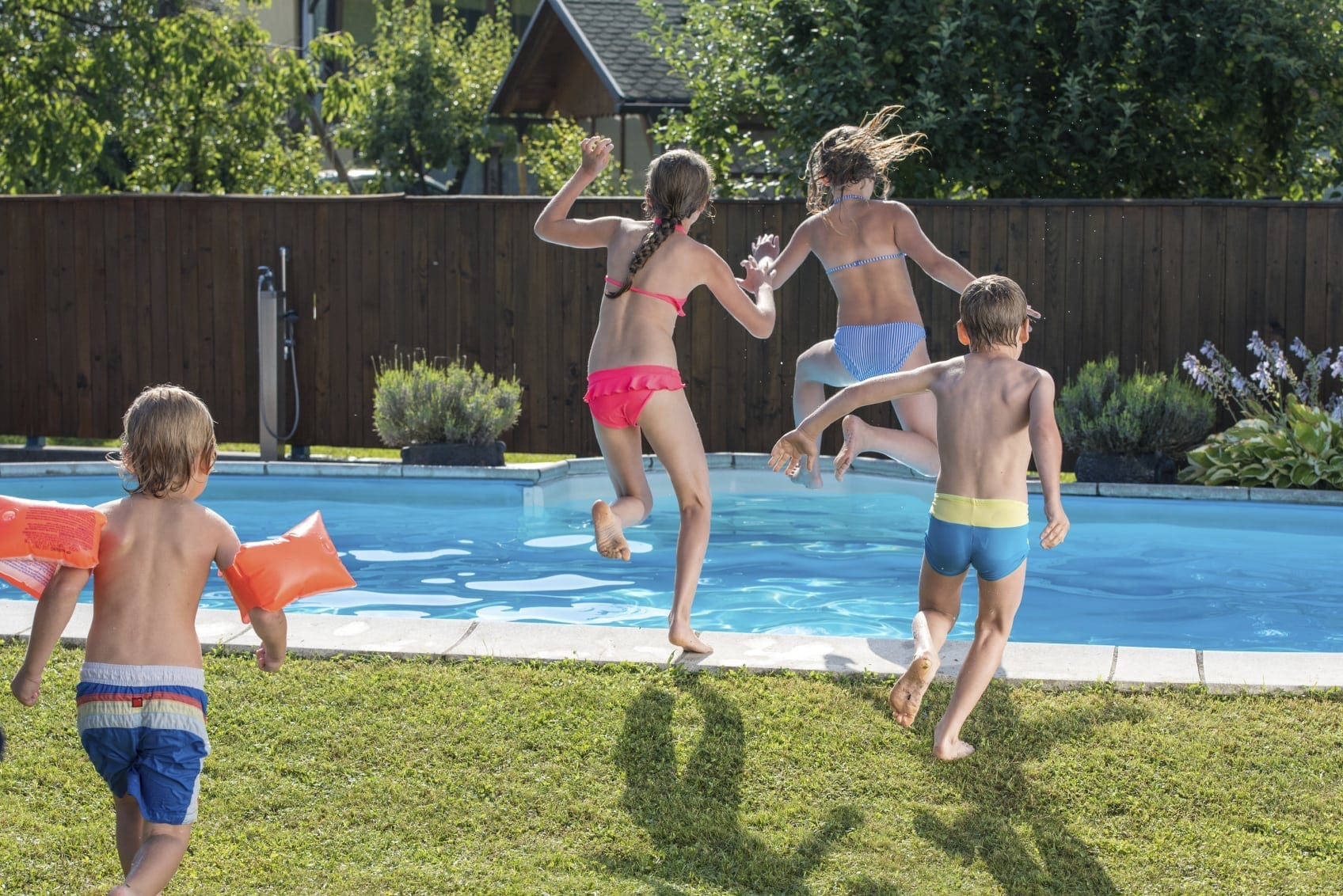 Young Children Jumping Into A Backyard Swimming Pool Stock Photo