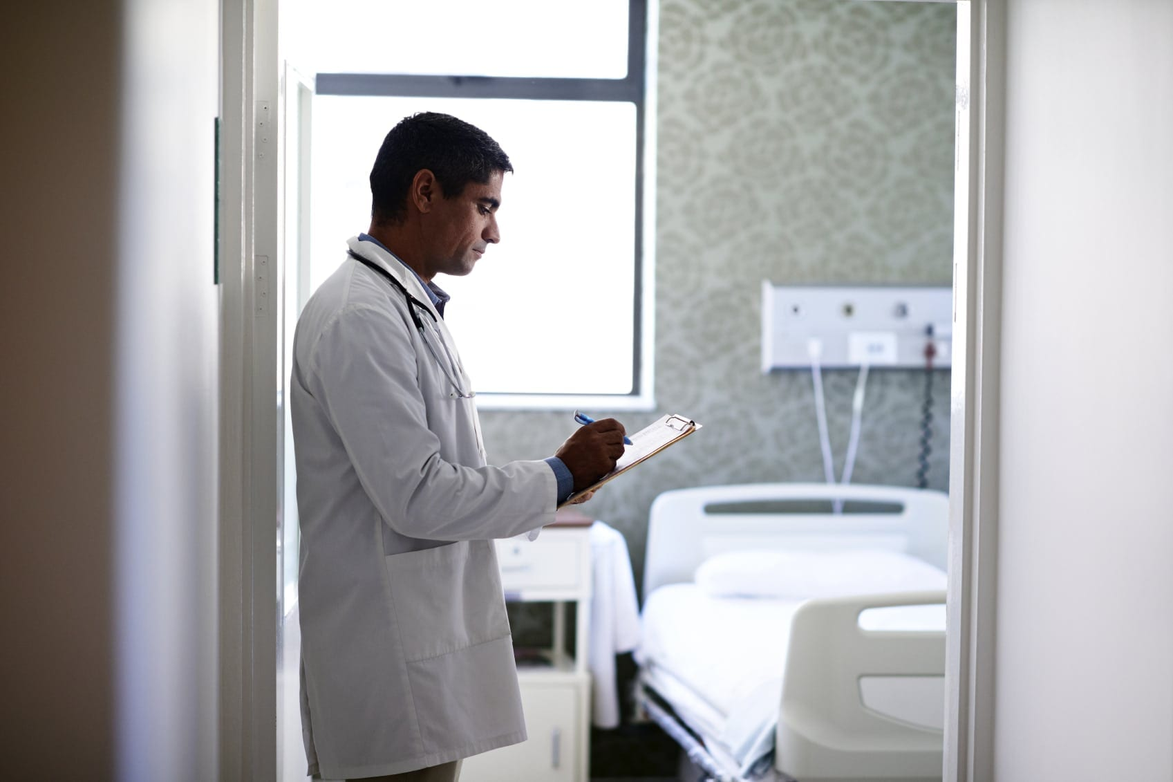 Male Doctor Completing Medical Forms In Hospital Room Stock Photo