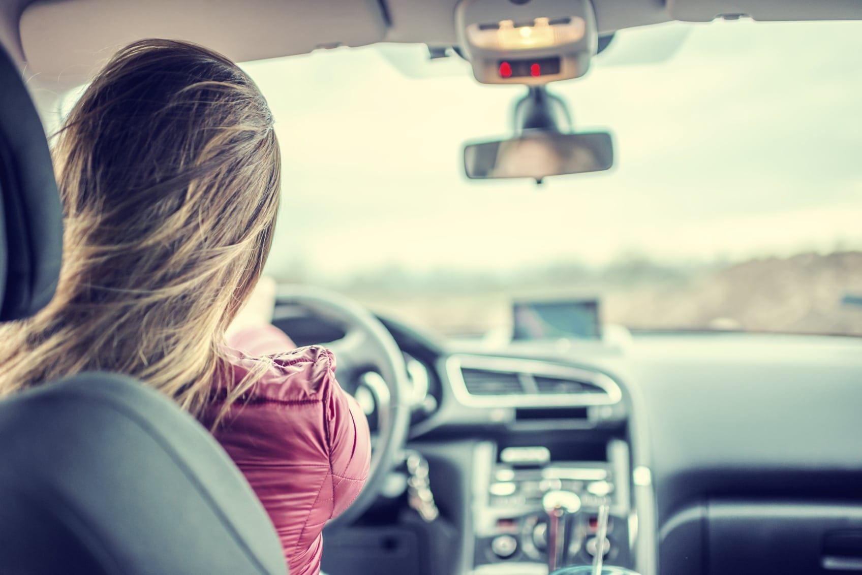 Young Female Driving Her Vehicle During The Day Stock Photo