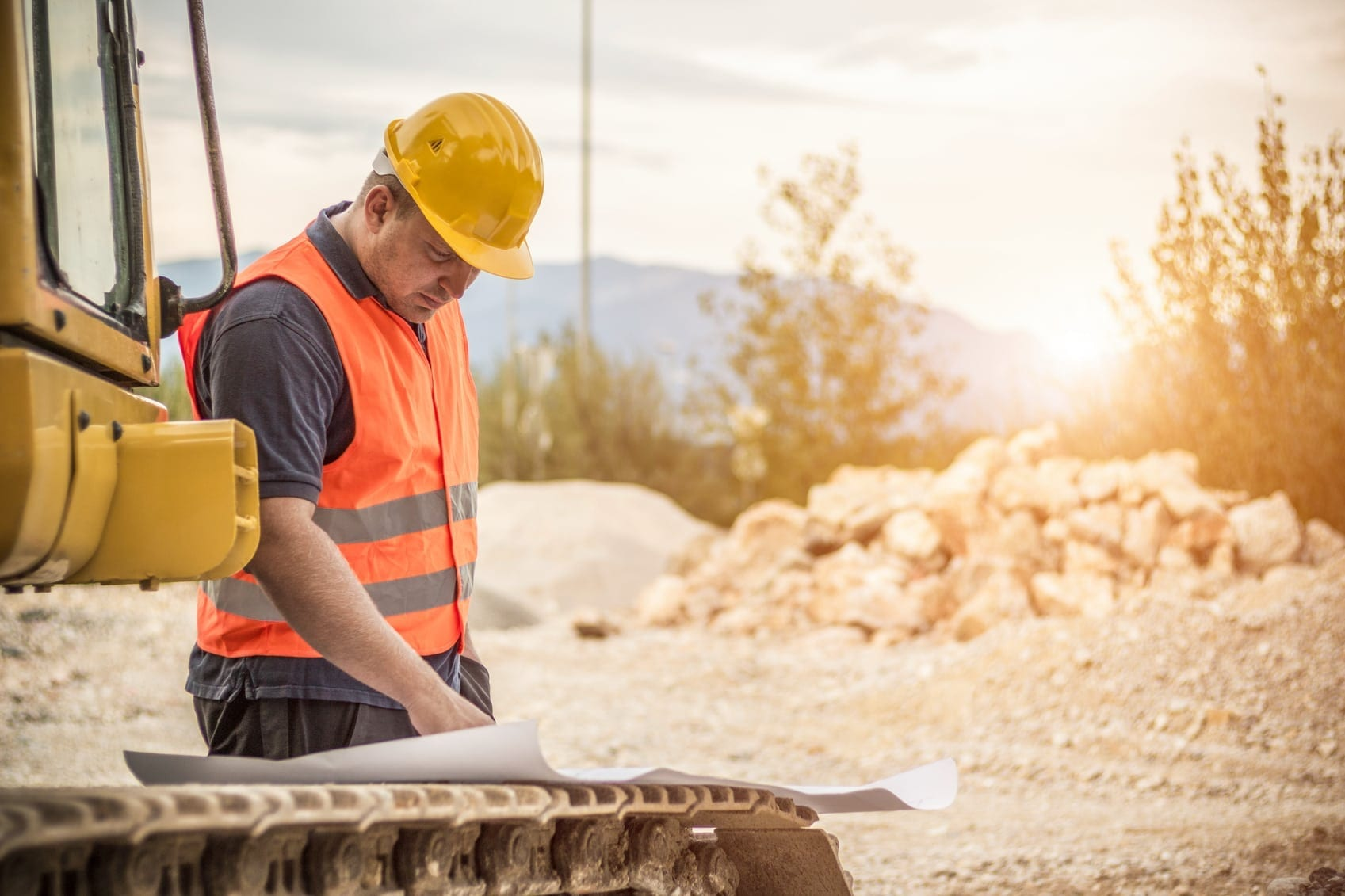 Construction Worker Reviewing Blueprints On A Job Site Stock Photo