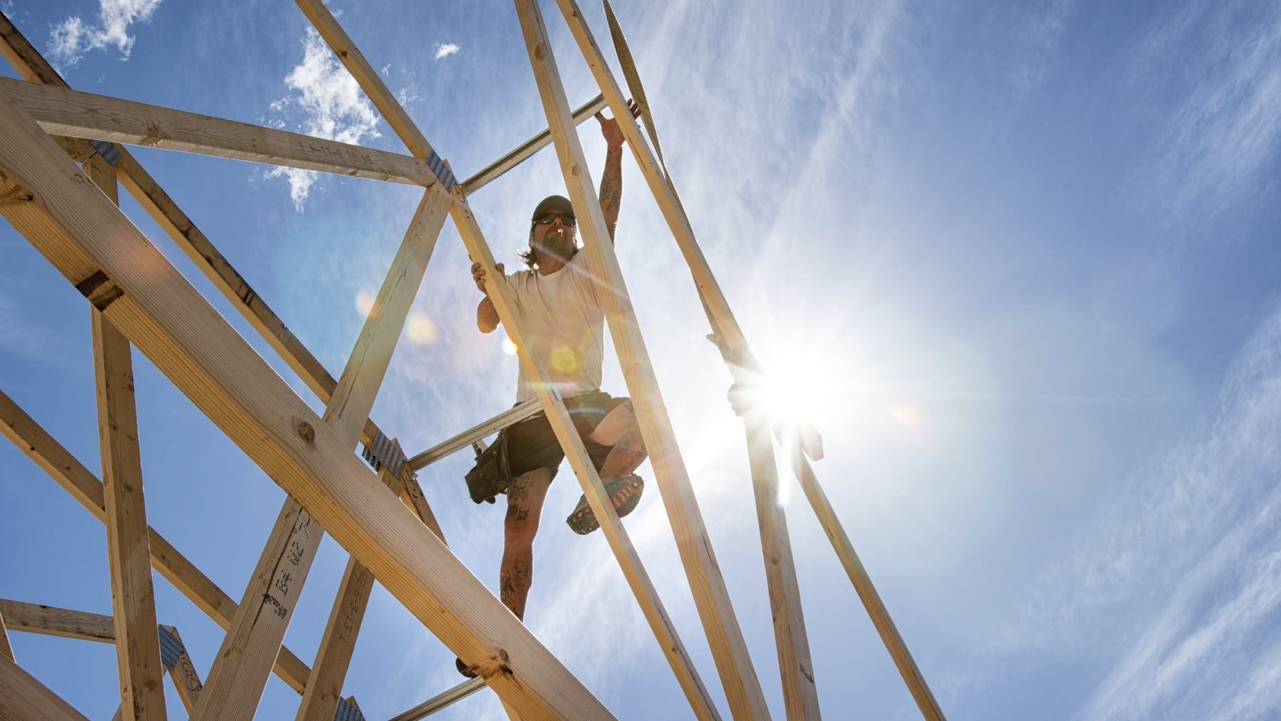 Construction Worker Climbing Structure Of Home Stock Photo