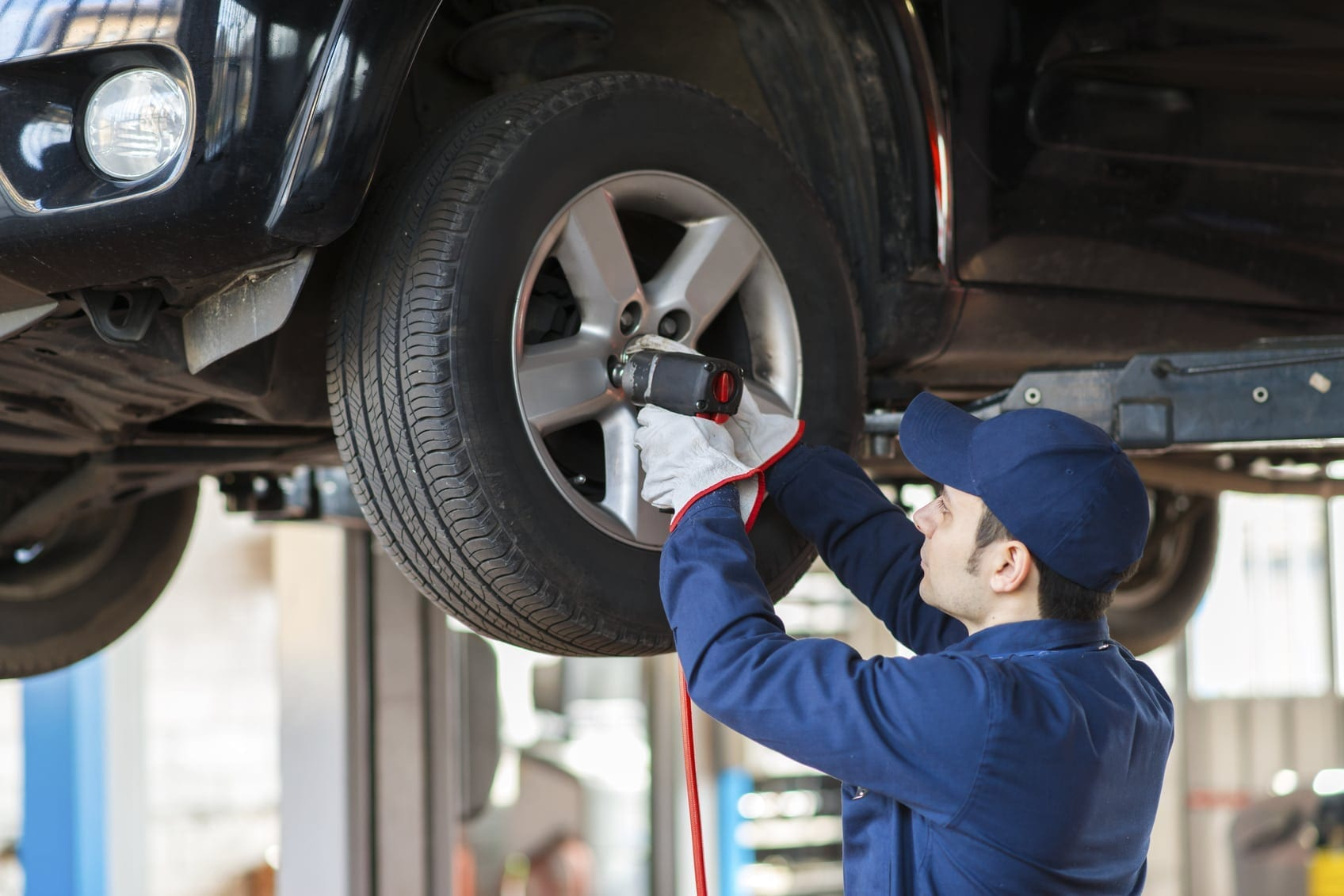 Mechanic Changing A Tire In An Auto Body Shop Stock Photo