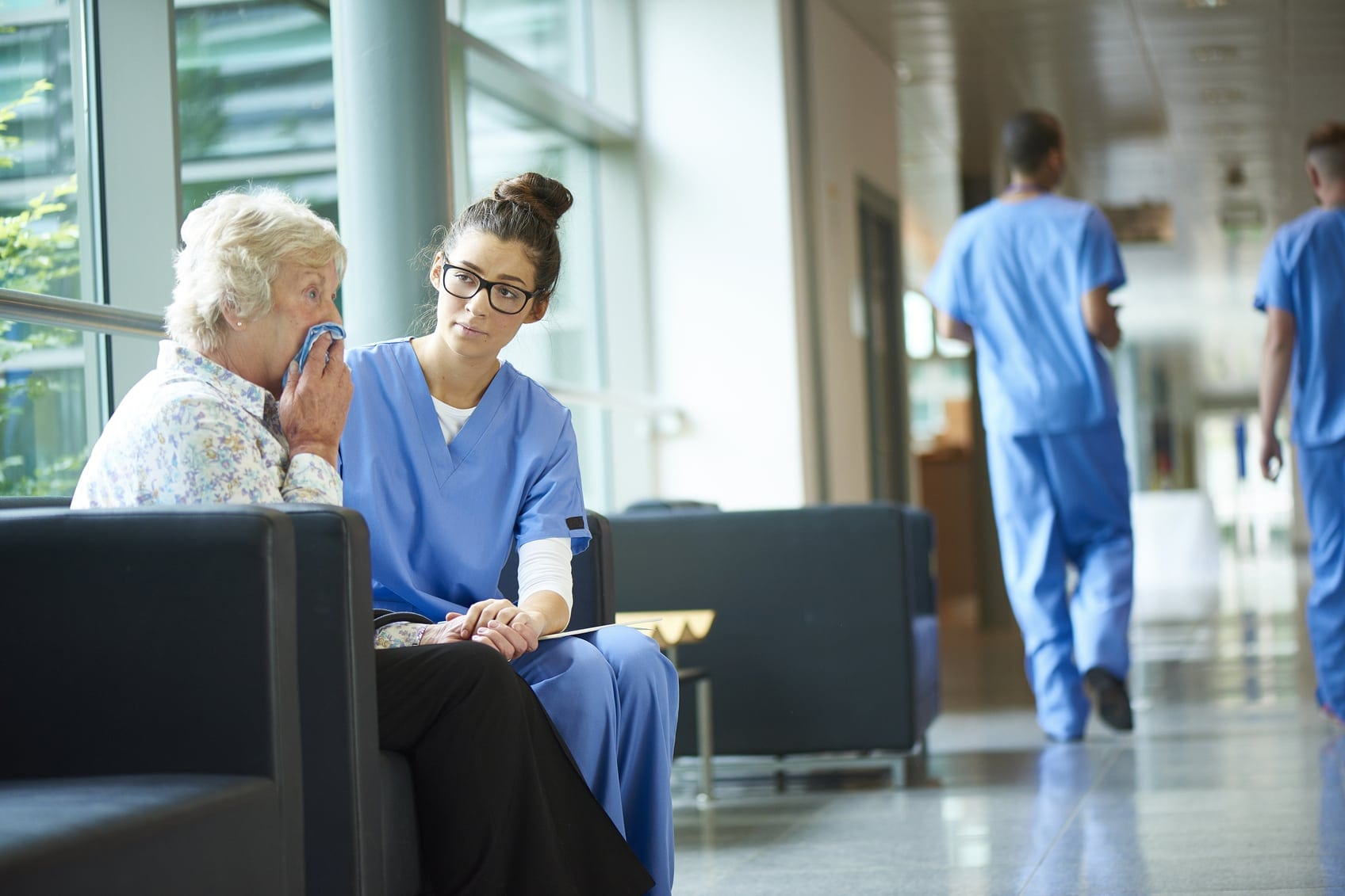 Female Nurse Consoling Elderly Female Patient Stock Photo