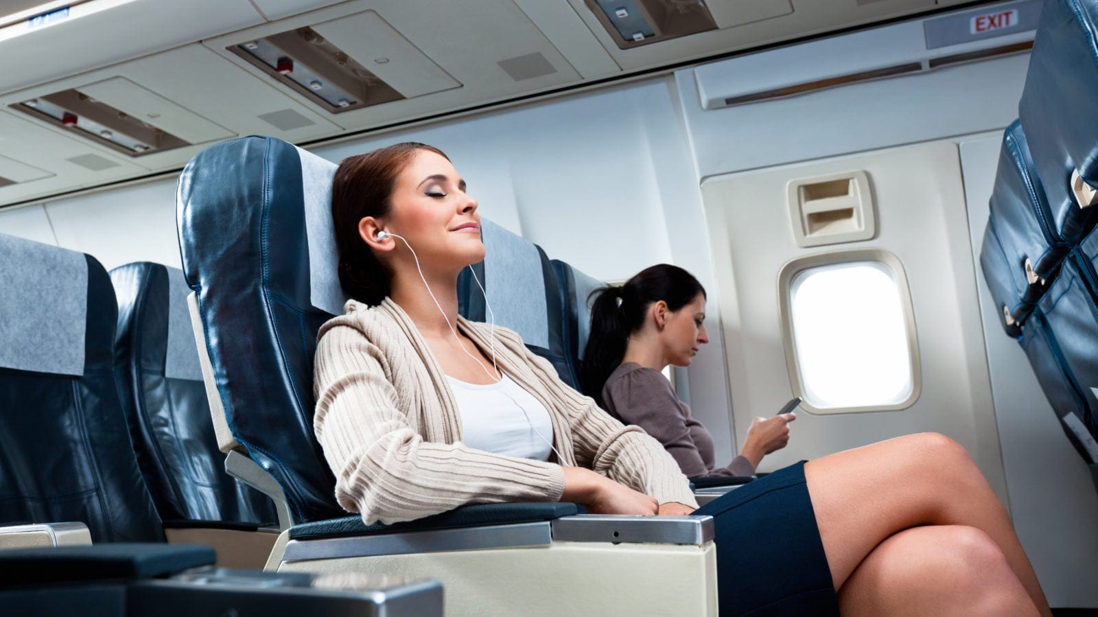 Female Passenger Relaxing On An Airplane Stock Photo