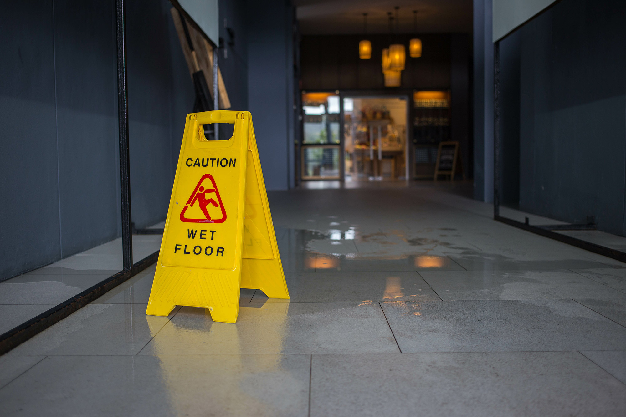 Wet floor sign next to puddle of water
