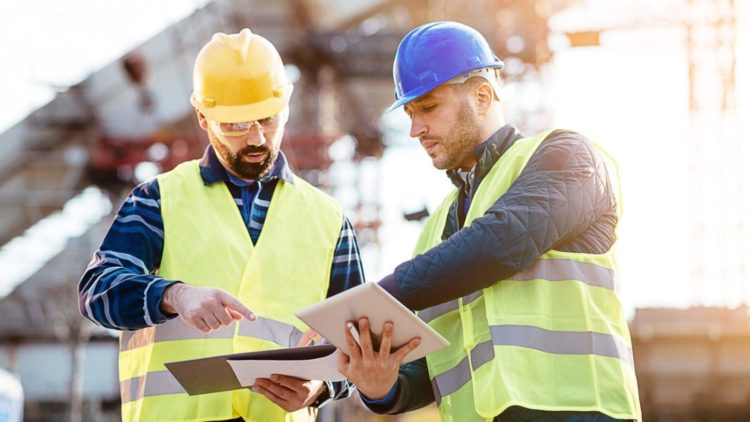 Engineer And A Construction Site Manager Examining A Blueprint Stock Photo