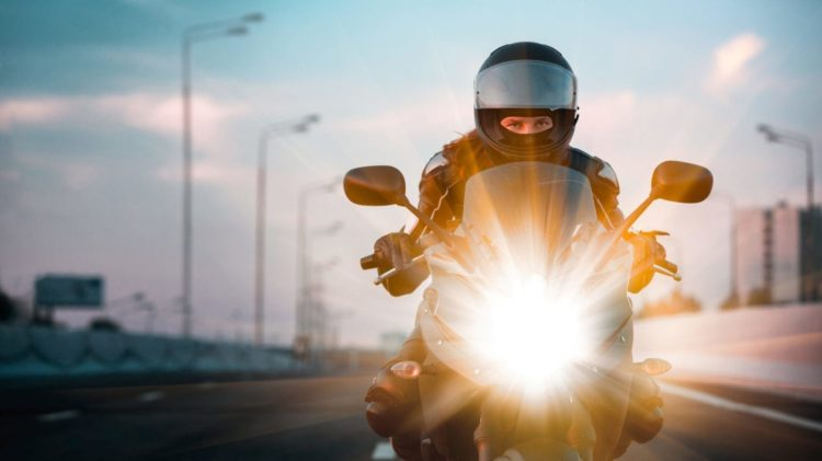 Female Motorcyclist Riding On The Highway Stock Photo