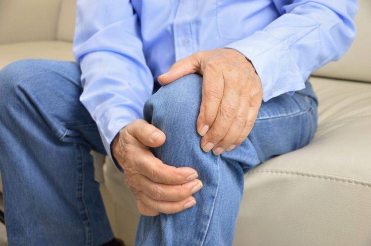 Elderly Man Experiencing Knee Pain Stock Photo