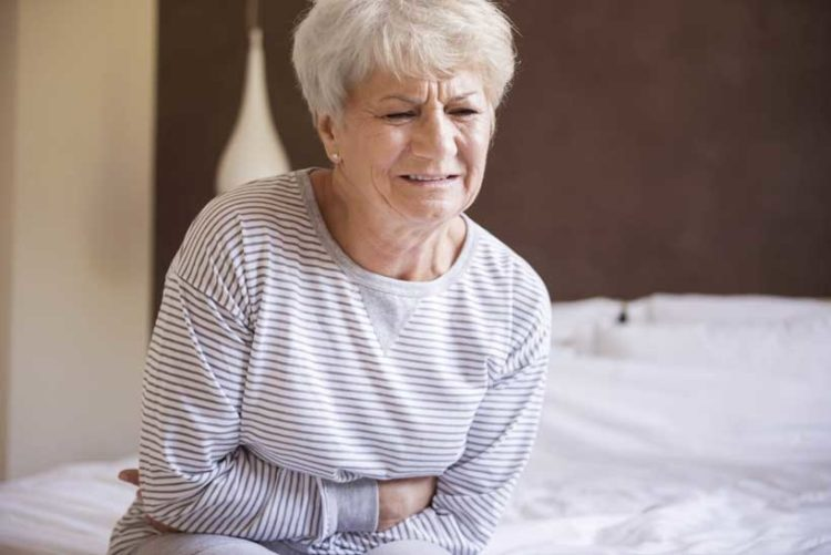 Elderly Woman Clutching Her Stomach In Pain