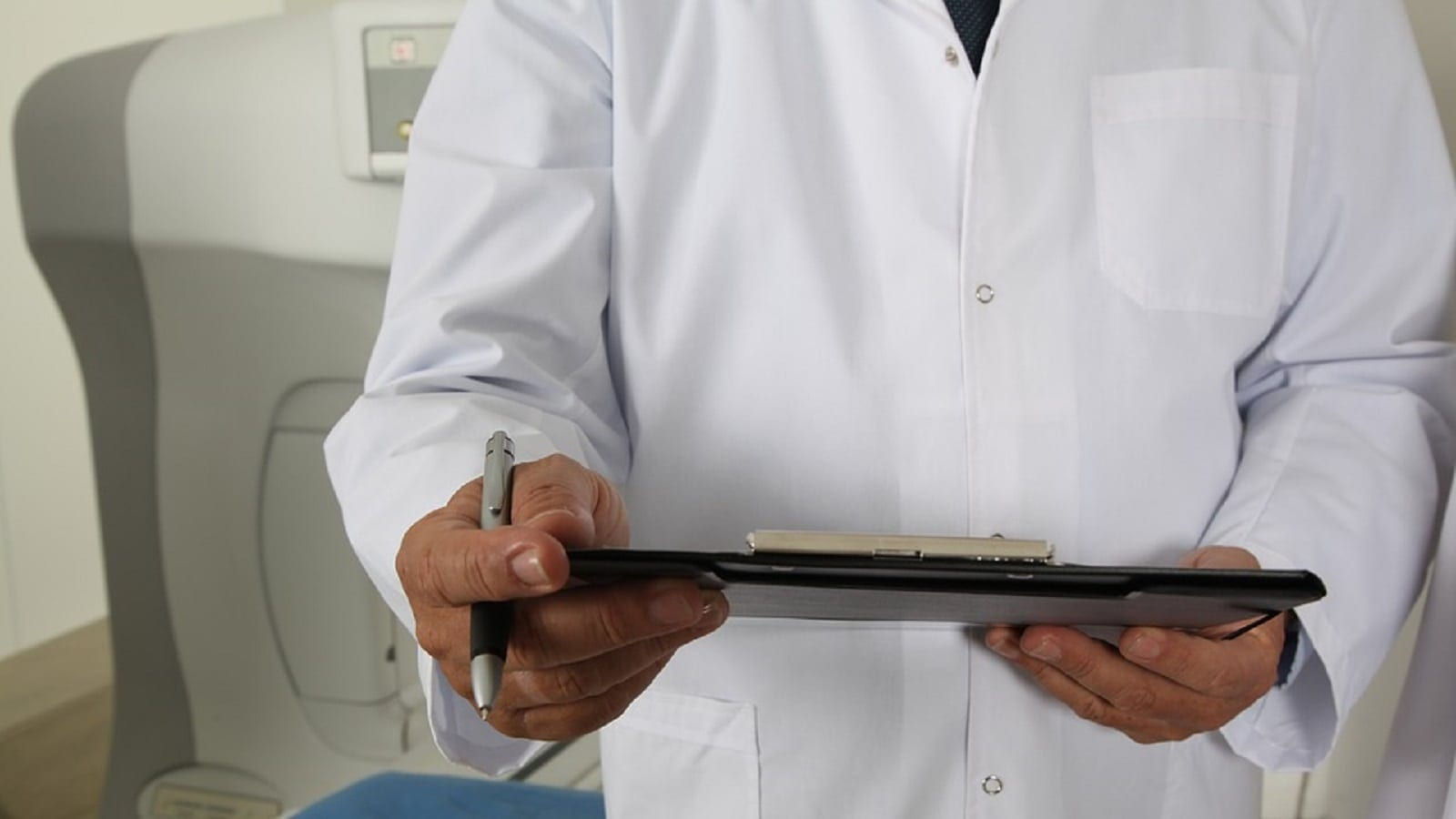 Doctor Filling Out Medical Forms Stock Photo