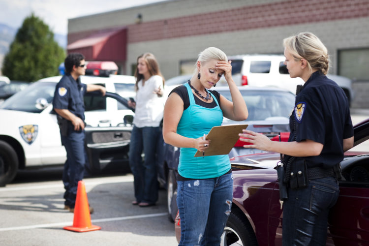 woman giving an accident report to police after a car accident