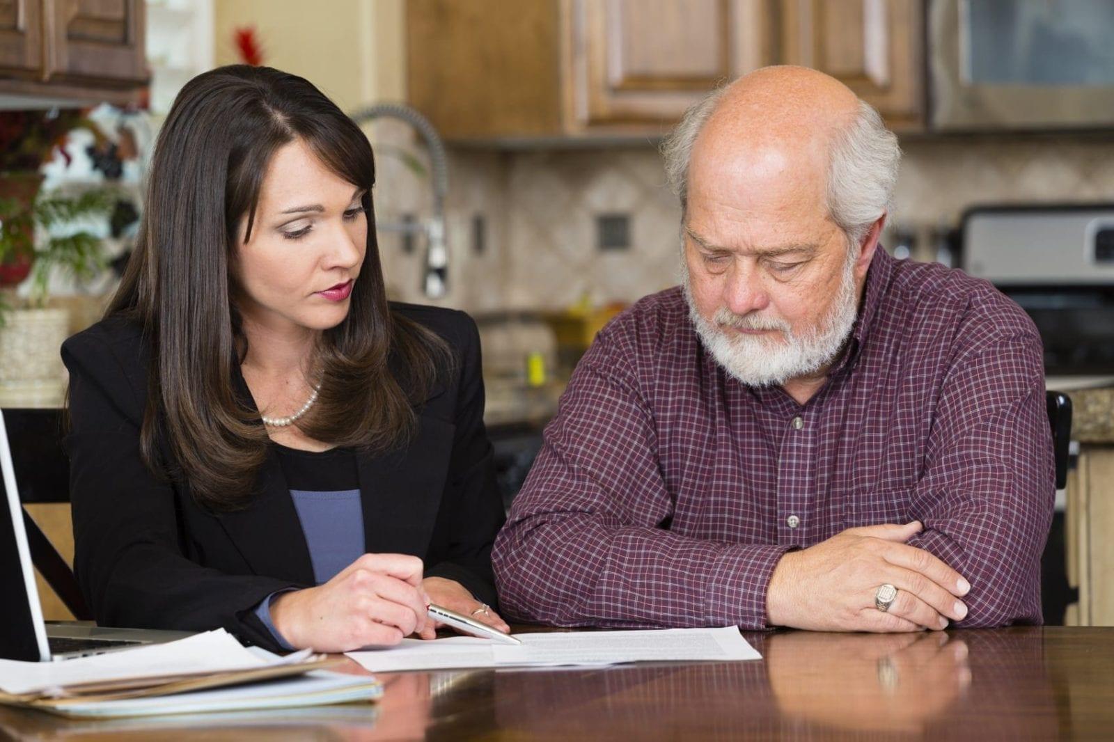 Female Attorney Advising Elderly Male Client Stock Photo