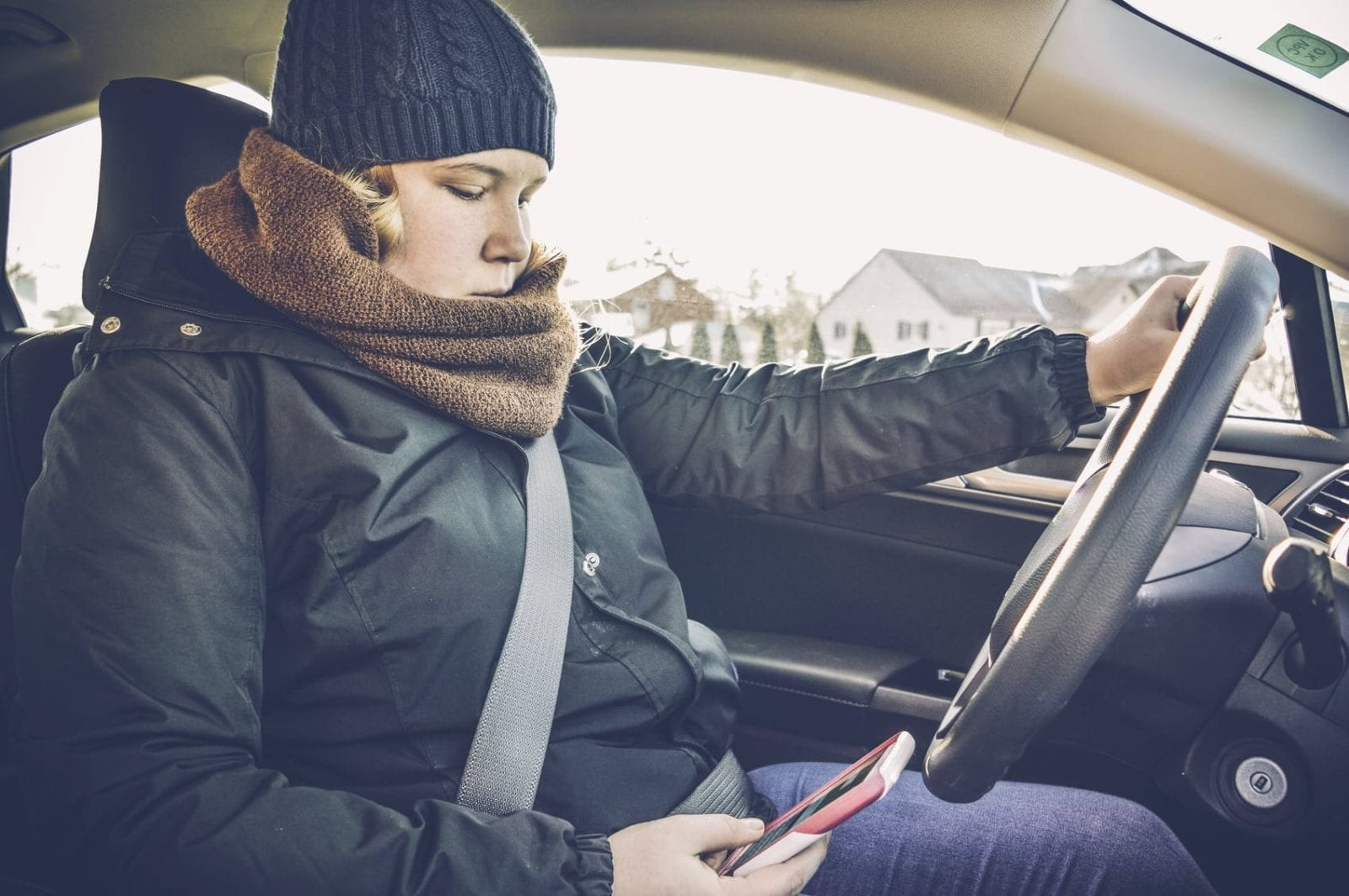 Teenage Girl Texting While Driving Her Vehicle Stock Photo