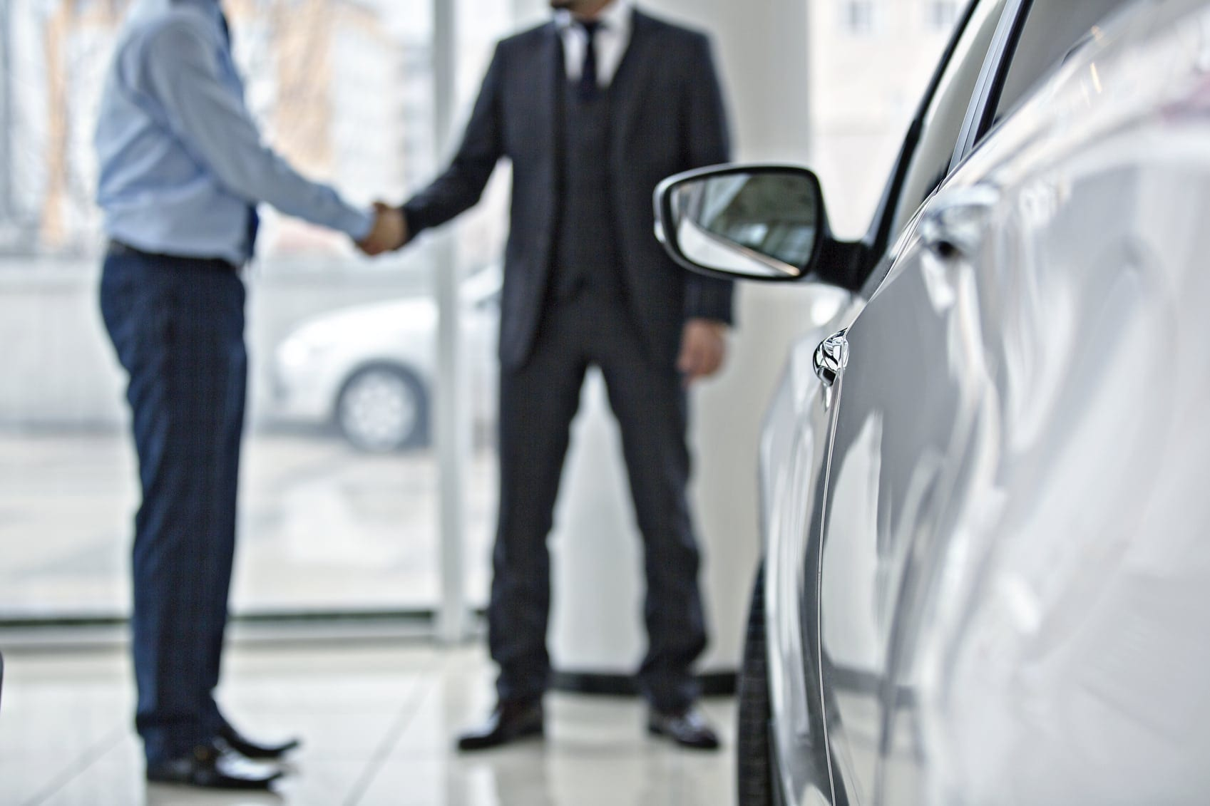 Car Buyer Shaking Hands With Car Salesman Stock Photo