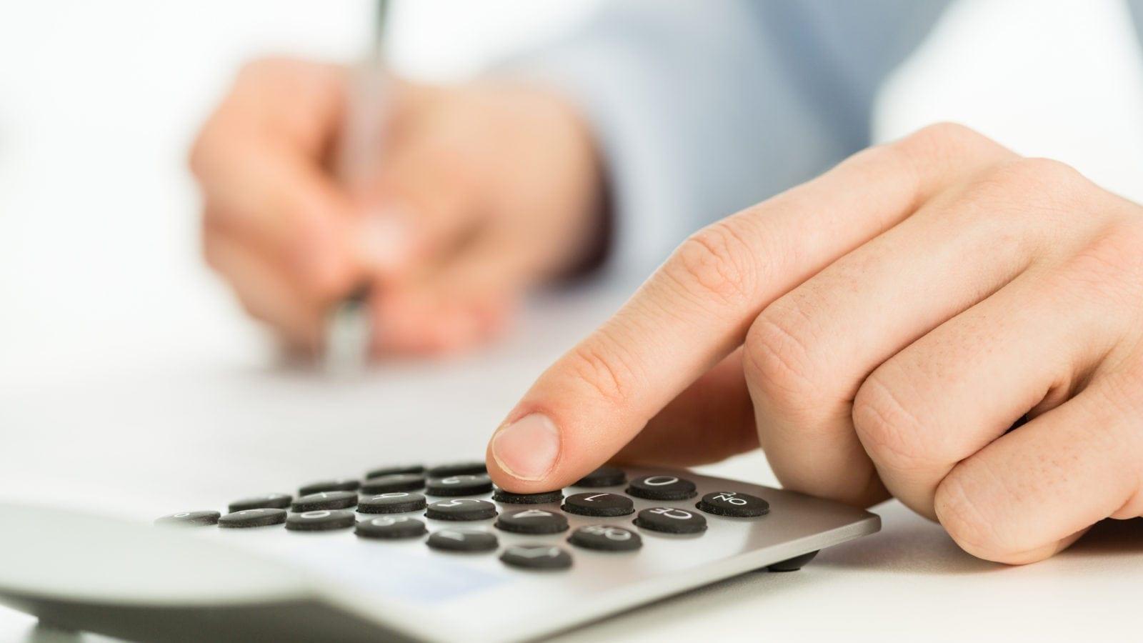 Hand On A Calculator Stock Photo