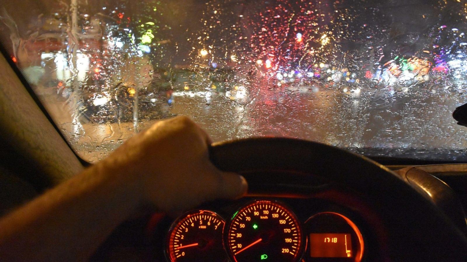 Man Driving His Car At Night In The Rain Stock Photo
