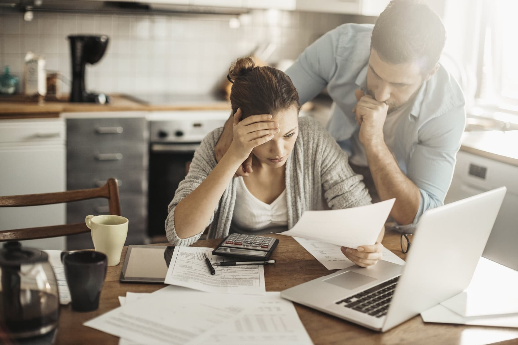 Distressed Couple Reviewing Bills At Their Table