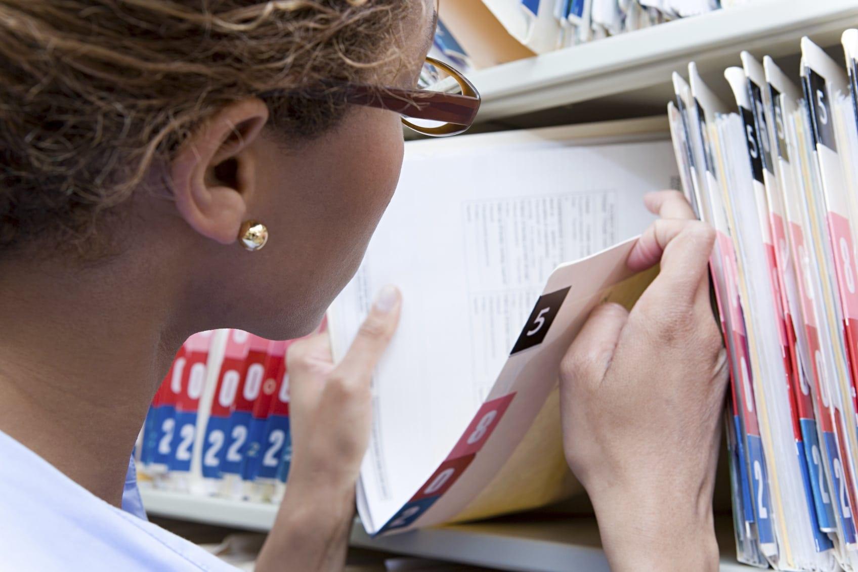 Nurse Examining Medical Records On Shelf Stock Photo