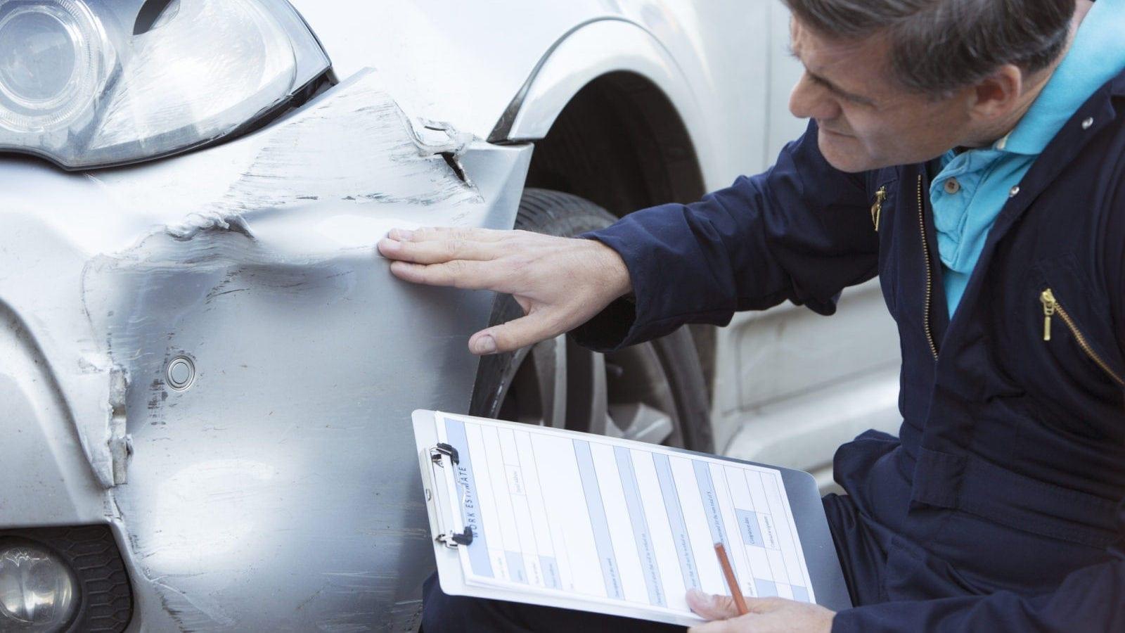 Auto Body Mechanic Writing An Estimate For Car Damage Stock Photo