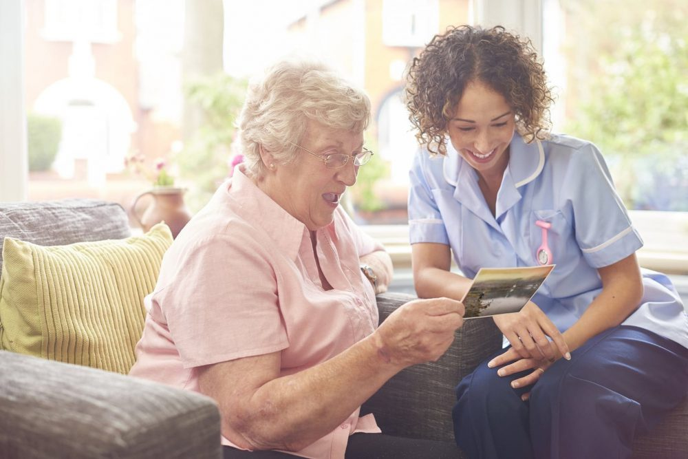 Female Nurse Spending Time With An Elderly Patient Stock Photo