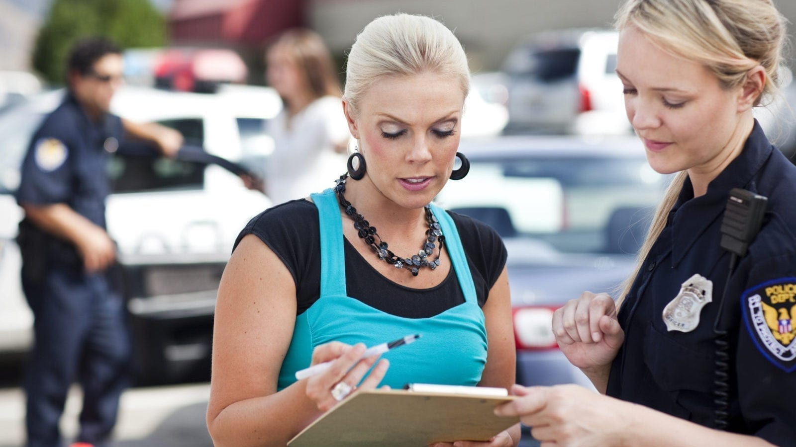 Woman Helping Complete An Accident Report With The Police Stock Photo