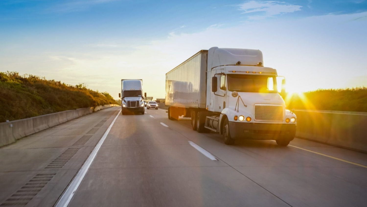 Semi-trucks Driving On The Interstate At Dusk Stock Photo