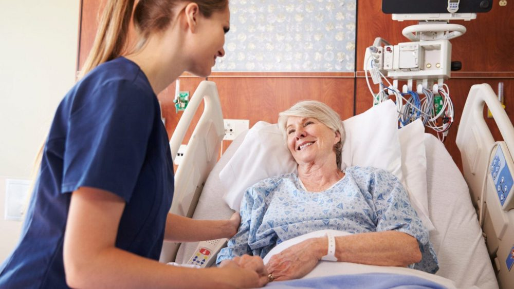 Nurse Talking To A Senior Female Patient In A Hospital Bed Stock Photo