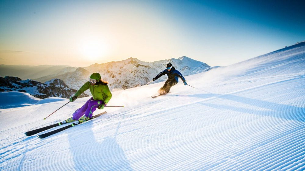 Male And Female Skiing Down A Mountain Stock Photo