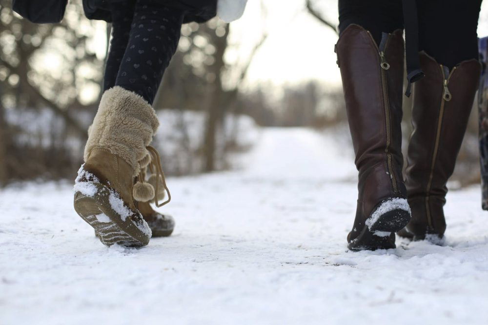 Women In Winter Boots Walking In The Snow Stock Photo