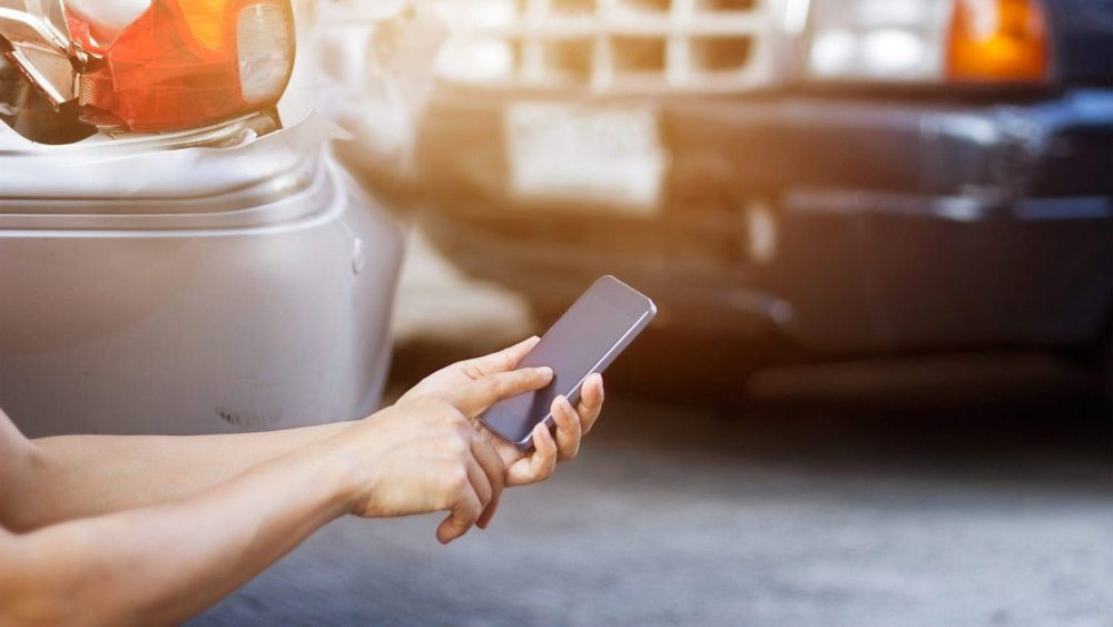 Man Using His Smart Phone To Report A Car Accident Stock Photo