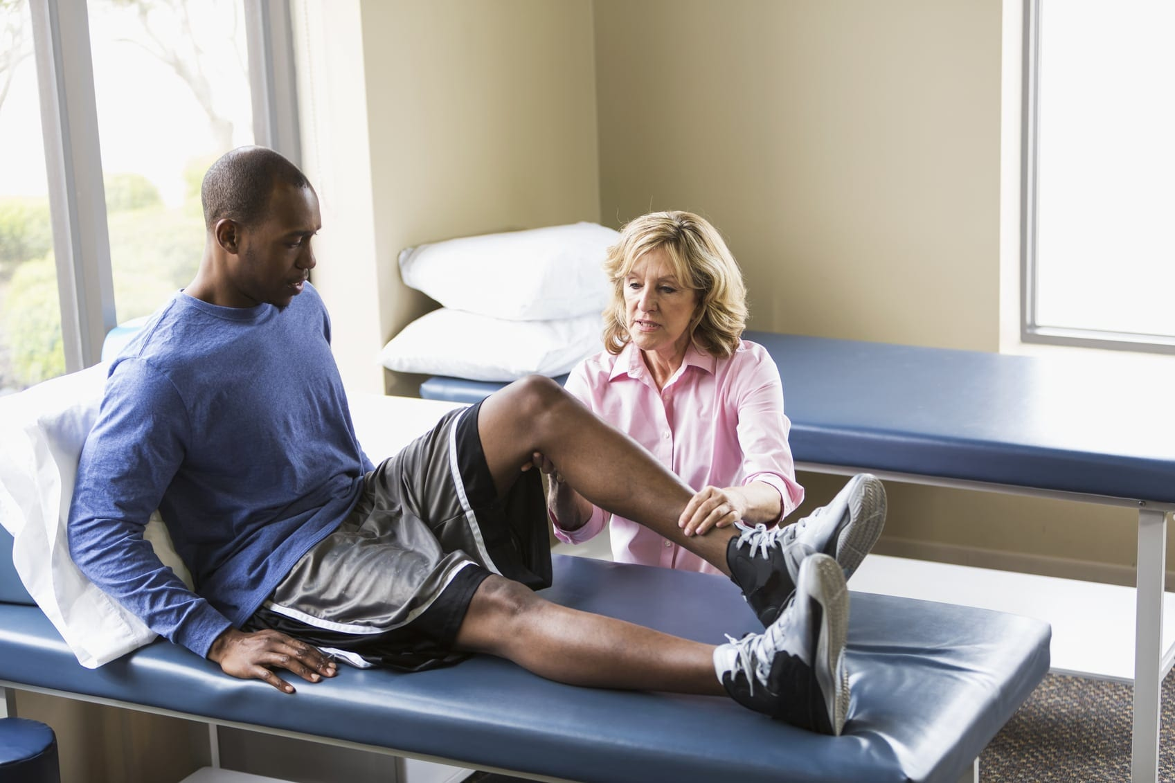 Man Having Leg Examined By Physical Therapist Stock Photo