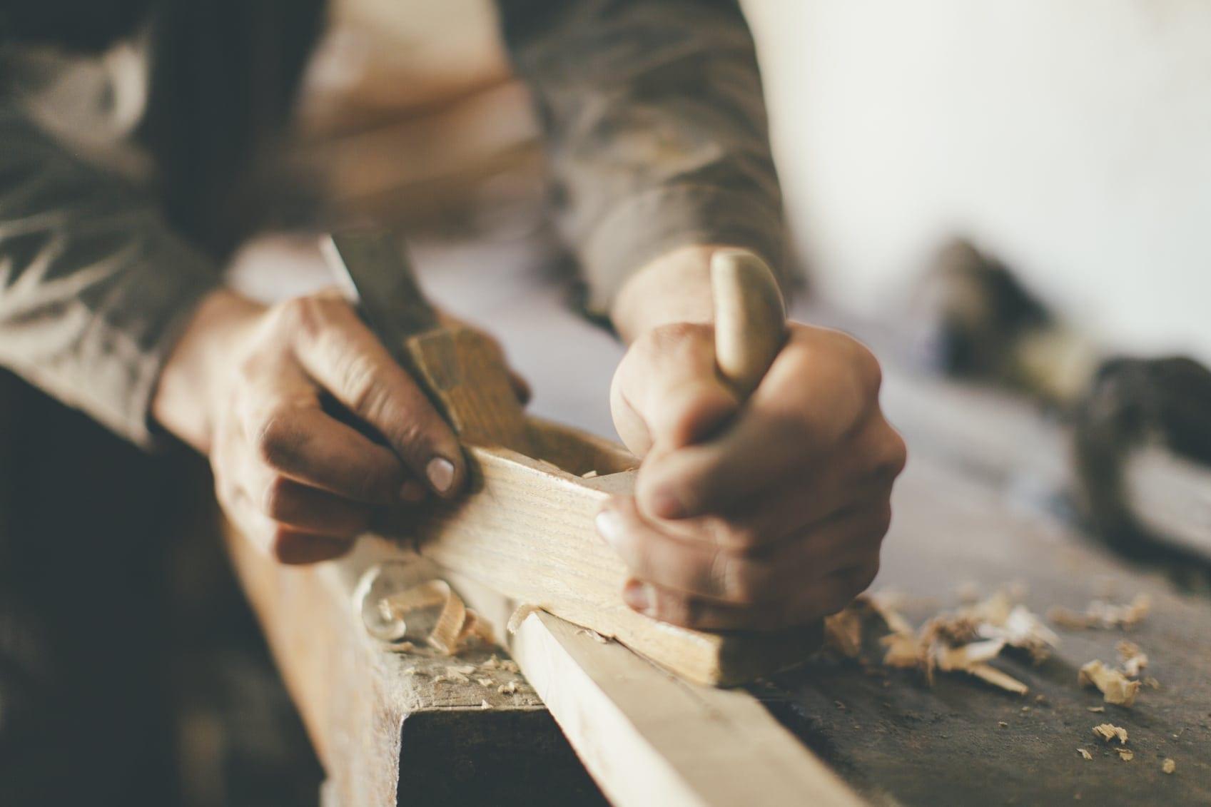 Man Cutting Wood Inside Wood Shop Stock Photo